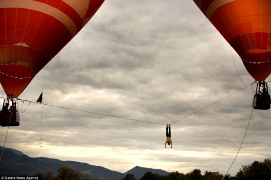 Daring Stomach Churning Tightrope Walk Between Flying Hot Air Balloons